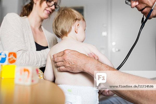 Baby (12-17 months) with mother and doctor in examination room