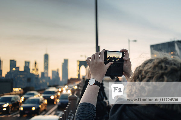 Woman taking picture of cityscape