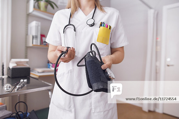 Young doctor in examination room holding blood pressure gauge