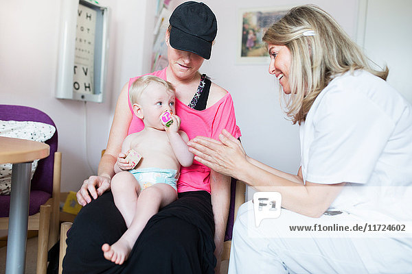 Baby (6-11 months) being examined by doctor Baby (6-11 months) being examined by doctor