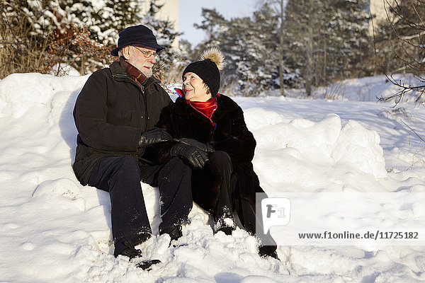 Senior couple walking in forest in winter