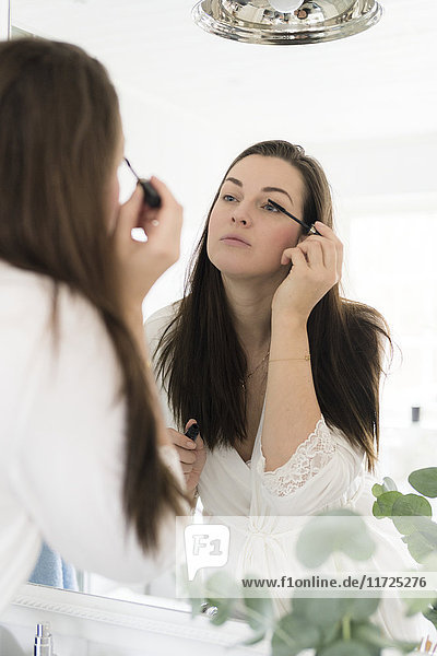 Woman in bathroom doing make-up