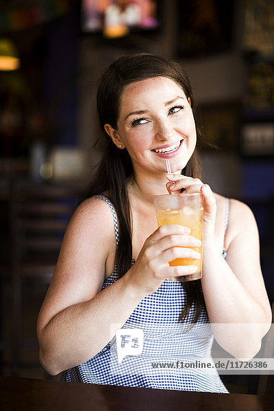 Portrait of woman drinking juice in cafe