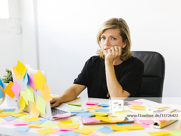 Portrait of Mature woman at office overwhelmed by adhesive notes