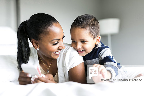 Mother and son (2-3) lying on bed and using smart phone