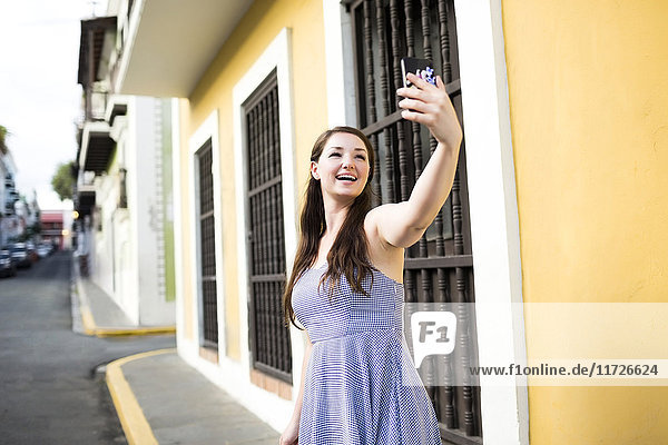 Puerto Rico  San Juan  Beautiful woman doing selfie on city street