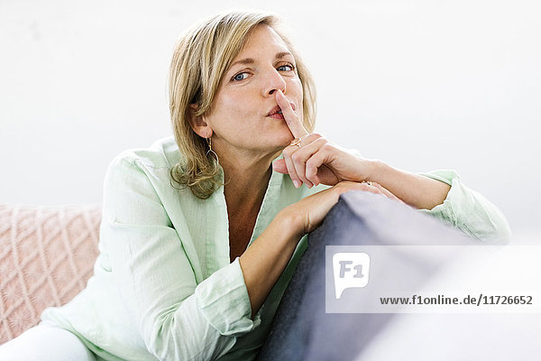 Portrait of woman sitting on sofa with finger on lips