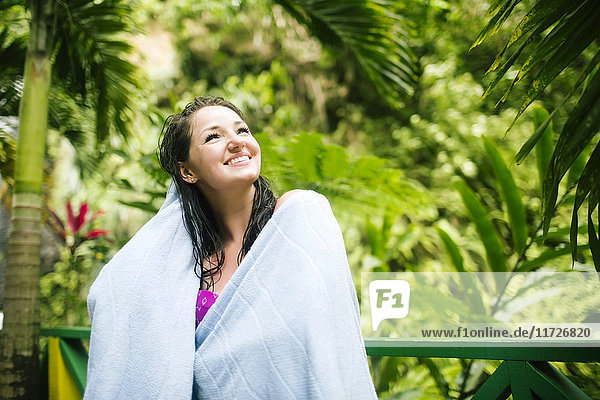 Caribbean Islands  Saint Lucia  Woman with wet hair wrapped in towel with lush foliage in background
