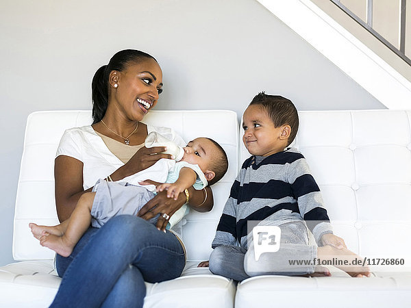 Mother with two sons (2-5 months  2-3) on sofa