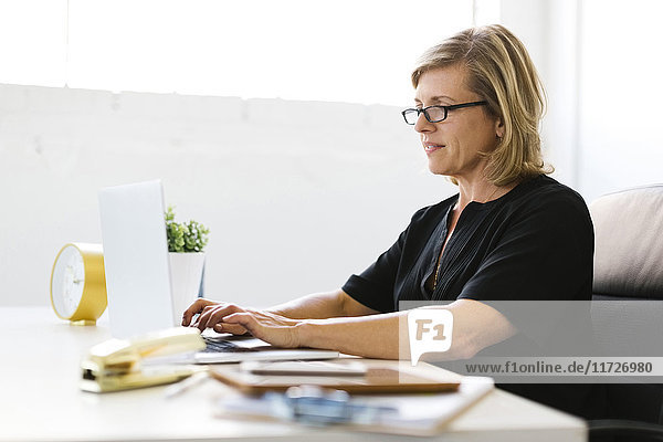 Mature woman in office typing on laptop
