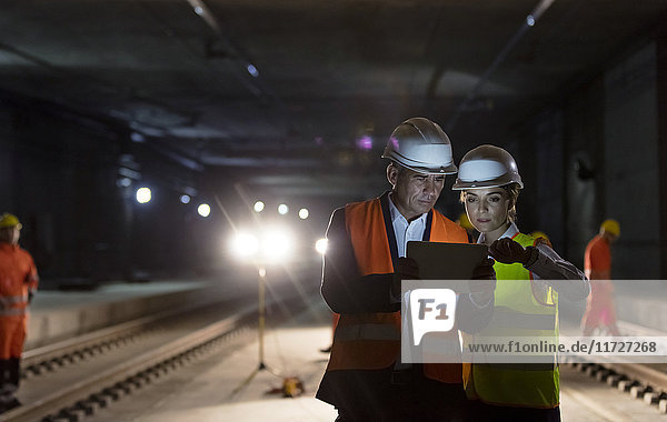 Foreman and construction worker using digital tablet at dark underground construction site