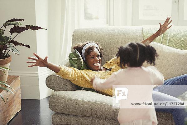 Enthusiastische Mutter auf dem Sofa Gruß läuft Tochter