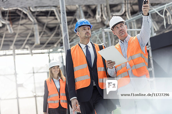 Businessman and engineer talking at construction site