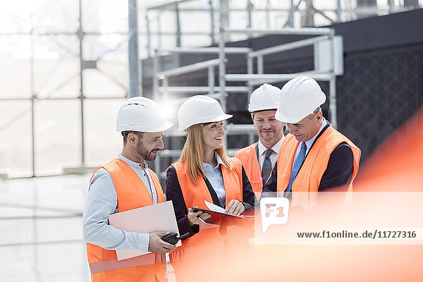 Foreman and engineers discussing paperwork at construction site