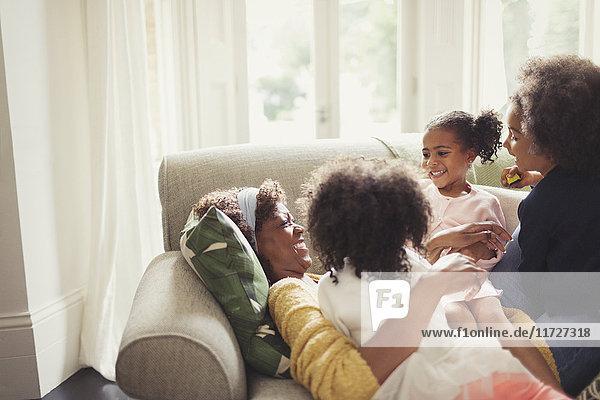 Zärtliche Töchter kuschelnde Mutter auf dem Sofa liegend