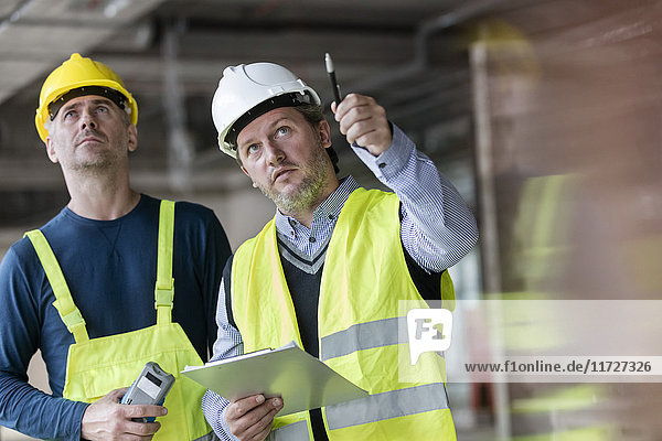 Male foreman and engineer with clipboard looking up at construction site