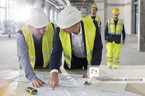 Male engineers discussing blueprints at construction site