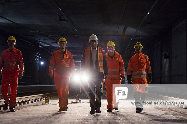Male foreman and construction workers walking in dark construction site underground