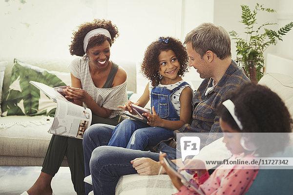 Multiethnische junge Familie mit digitalen Tabletts und Lesemagazin auf dem Sofa