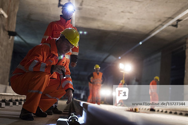 Male construction workers examining underground tracks at dark underground construction site