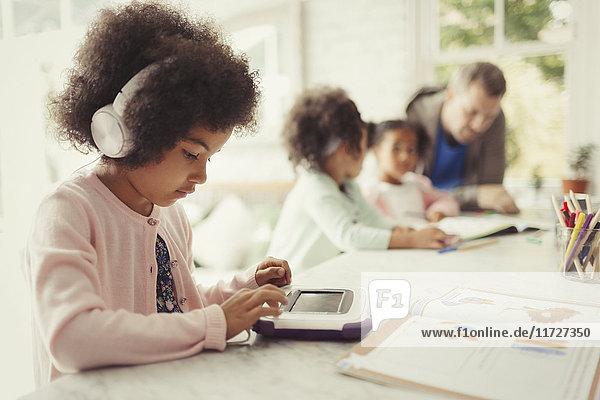 Mädchen mit Kopfhörer mit digitalem Tablett bei den Hausaufgaben am Tisch