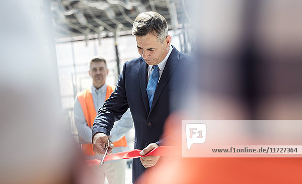 Businessman cutting ribbon at new construction site ceremony