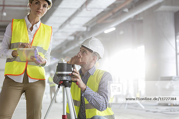 Engineers with digital tablet and theodolite surveying construction site