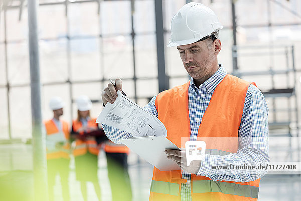 Male engineer reviewing blueprints on clipboard at construction site