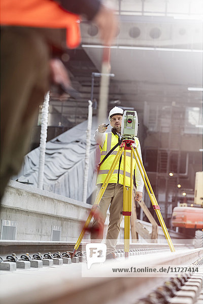 Male engineer using theodolite on tracks at construction site