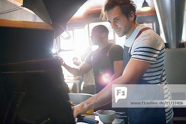 Fokussierte männliche Kaffeeröster arbeiten mit dem Computer
