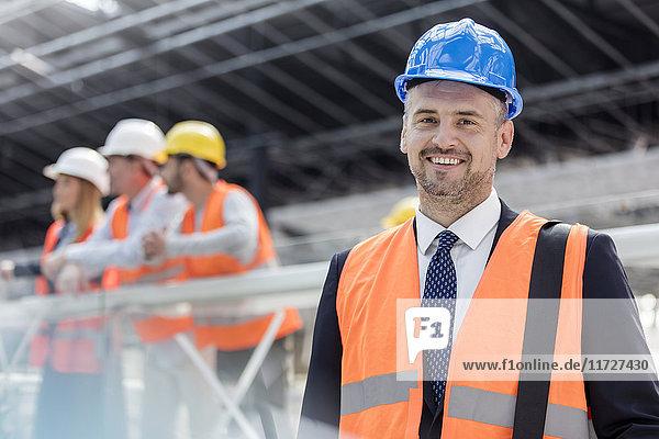 Portrait confident businessman in hard-hat at construction site