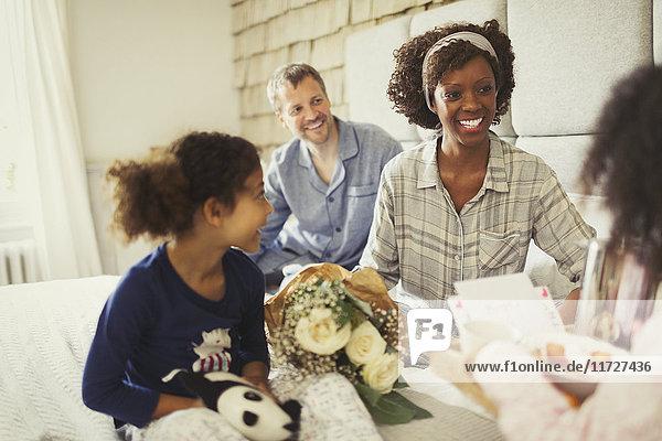 Töchter bringen Muttertag Blumen und Frühstück zu Mutter im Bett
