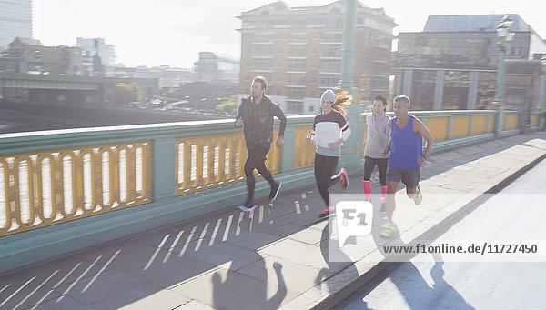 Läuferinnen und Läufer auf einer sonnigen Stadtbrücke