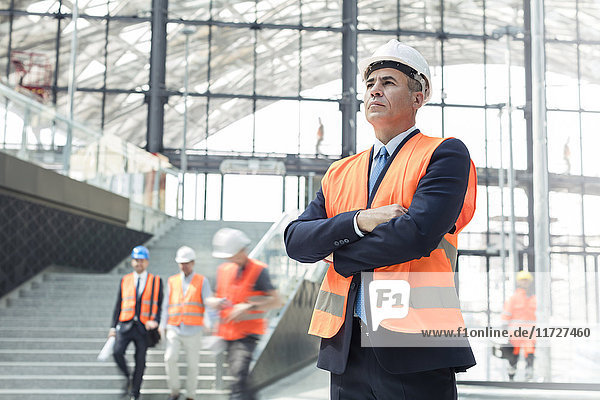 Serious businessman wearing hard-hat at construction site