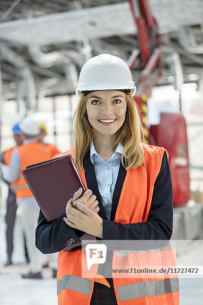 Portrait smiling female engineer at construction site