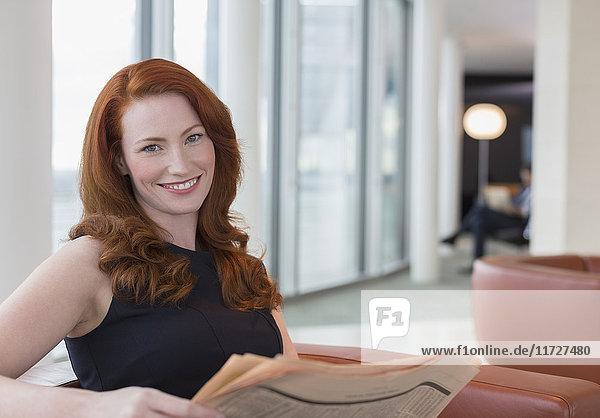 Portrait lächelnde Geschäftsfrau mit roten Haaren in der Bürolounge