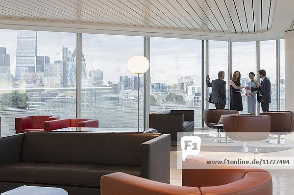 Geschäftsleute treffen sich an Fenstern in der urbanen Hochhauslounge