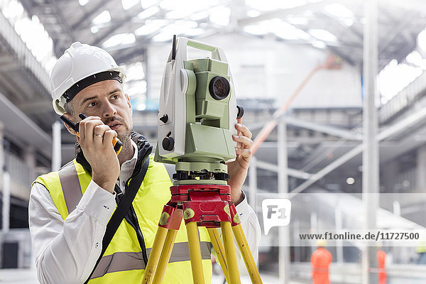 Male engineer using walkie-talkie and theodolite at construction site