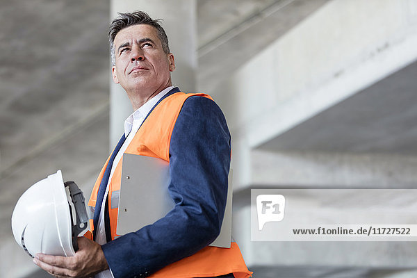 Serious businessman with hard-hat at construction site