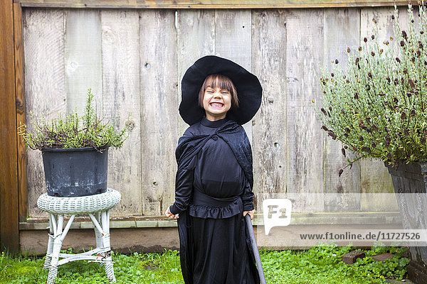 Portrait begeistertes Mädchen in Hexenkostüm im Garten