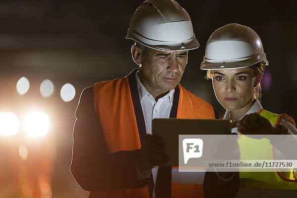 Construction worker and engineer using digital tablet at dark construction site