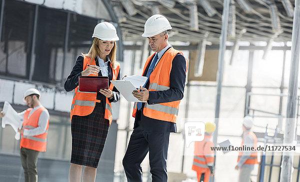 Ingenieure mit Klemmbrettern treffen sich auf der Baustelle