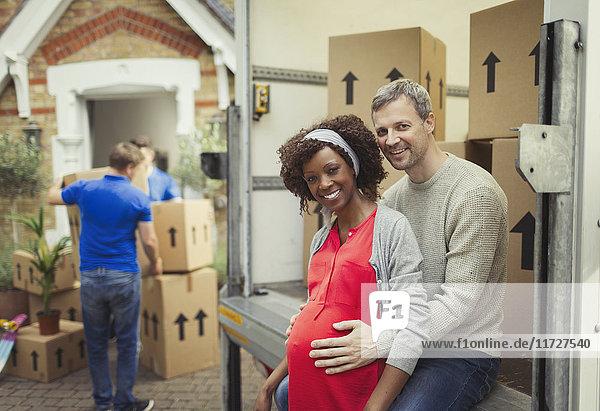 Portrait lächelndes schwangeres Paar beim Umzug vor dem neuen Haus