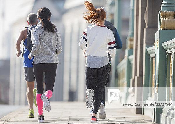 Läuferinnen und Läufer auf dem sonnigen Bürgersteig der Stadt