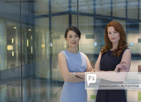 Portrait selbstbewusste Geschäftsfrauen im modernen Büroatrium