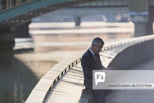 Geschäftsmann beim SMSen mit Handy an der städtischen Hafenpromenade