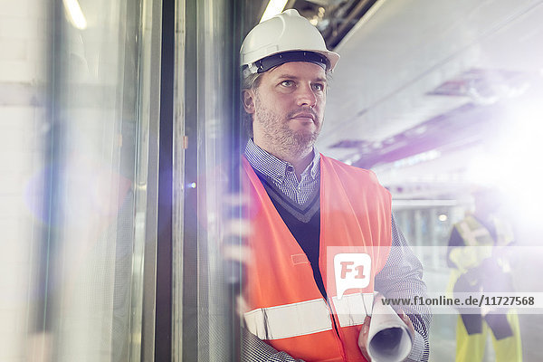 Serious male engineer with blueprints at construction site