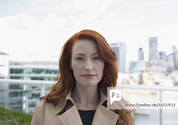 Portrait serious  confident businesswoman with red hair on urban balcony with city view