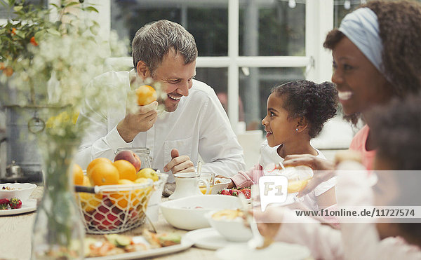 Multi-ethnischer Vater und Tochter beim Frühstücken am Tisch
