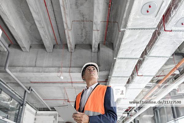 Foreman with clipboard looking up at construction site